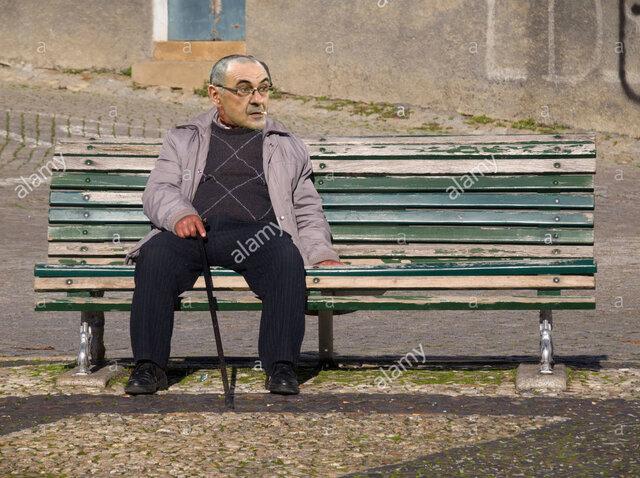 lone-vecchio-seduto-su-una-panchina-nel-parco-d060y6.jpg